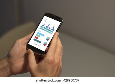 Two hands of young man holding smartphone with graphical data on the screen (column graph, stacked bar graph and pie graph).
