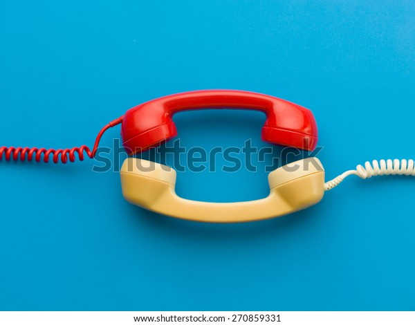 two handsets facing each other on blue background