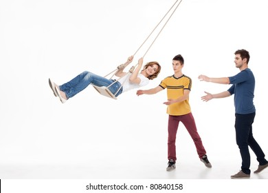 two handsom men pushing on the swing one smiling woman