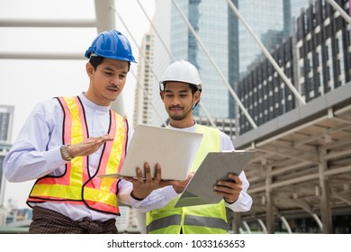 Two Handsome Burmese or Myanmar engineer with longyi traditional dress using computer laptop to check construction project plan progress in Bangkok Modern city. Industrial concept.
