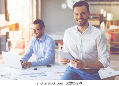 Two handsome businessmen in classic shirts are using gadgets and smiling while working in office