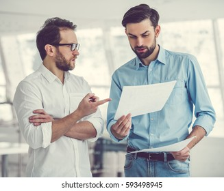Two handsome businessmen are examining and discussing documents while standing in office