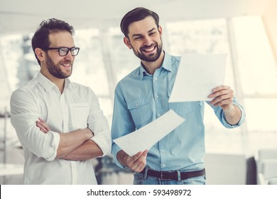 Two handsome businessmen are examining documents, talking and smiling while standing in office