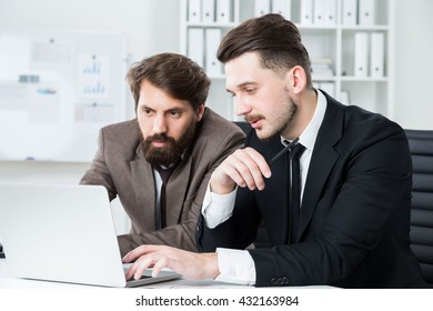 Two handsome businessmen in office discussing business project on computer laptop