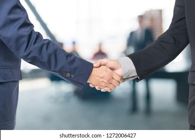 Two Handsome Businessmen Shaking hand to appreciate each other in Office Meeting Room Background as Business Partner or Teamwork Greeting Concept.