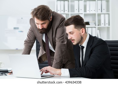 Two handsome businessmen sitting and standing at office desk discussing business project on laptop