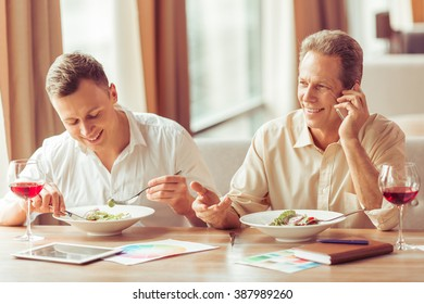 Two handsome businessmen are smiling during business lunch at the restaurant. Middle aged man is talking on the mobile phone