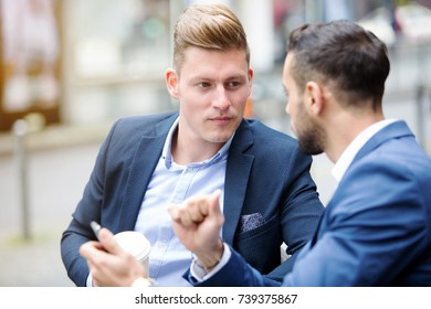 two handsome businessmen talking outside in the street