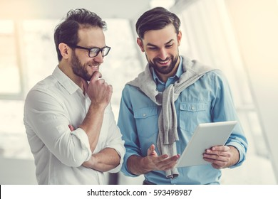 Two handsome businessmen are using a digital tablet and smiling while standing in office