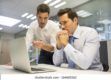 Two handsome businessmen working together on a project in the office