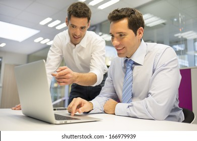 Two handsome businessmen working together on a Laptop in the office