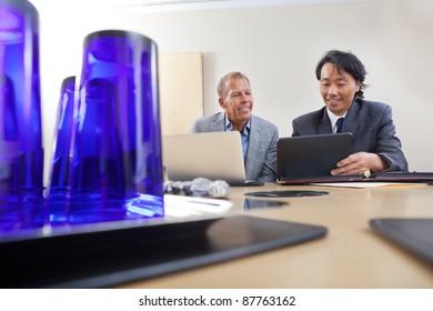 Two handsome businessmen working together on a laptop and digital tablet