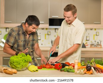 two handsome caucasian men in kitchen, pretending to cut one's finger off