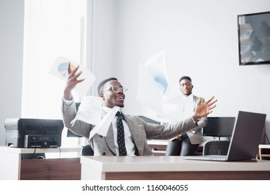Two handsome cheerful african american businessman celebration successful with throwing paper in workplace.