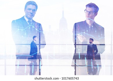 Two handsome european businessmen standing on abstract city background with forex chart. Teamwork and trade concept. Double exposure