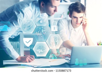 Two handsome european businessmen using laptop with glowing interface together. Teamwork and innovation concept. Double exposure