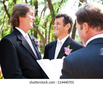 Two handsome gay grooms getting married  in beautiful park-like setting.
