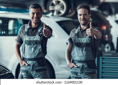 Two Handsome Happy Auto Mecanics Keeping Thumbs up. Excited Attractive Repairmen in Grey Uniform Showing Positive Emotions Standing in Garage with Cars. Repair Service Concept.
