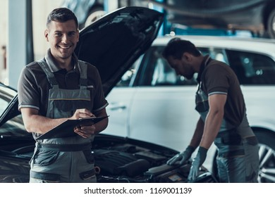 Two Handsome Happy Auto Mecanics in Garage. Portrait of Attractive Repairmen in Uniform Showing Positive Emotions while Doing Job Filling Car Checkup Form after Inspection . Repair Service Concept.