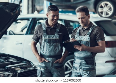 Two Handsome Happy Auto Mecanics in Garage. Portrait of Attractive Repairmen in Grey Uniform Showing Positive Emotions Filling Car Checkup Form after Inspection . Repair Service Concept.