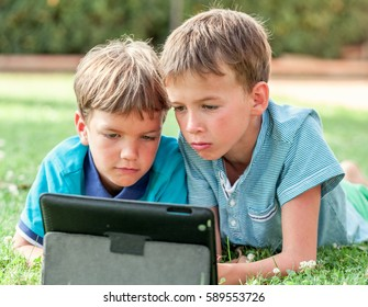 Two handsome happy boys lying with tablet on green grass, elder and younger brother in summer park, outdoor