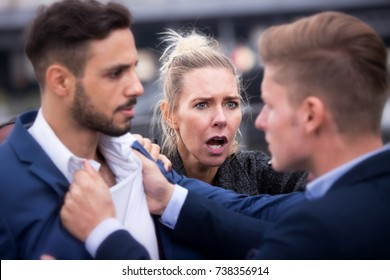 two handsome man fighting while a woman is trying to intervene