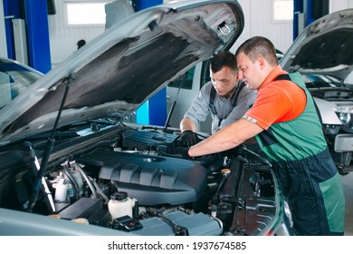 Two handsome mechanics in uniform are working in auto service. Car repair and maintenance