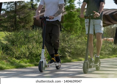 Two handsome men riding electric kick scooters at beautiful park landscape