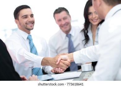 Two handsome men shaking hands with smile while sitting on the c