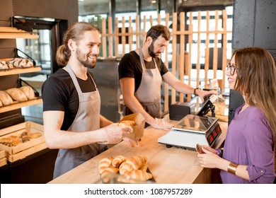 Two handsome sellers in uniform selling bread to a young woman client standing at the counter of the bakery shop