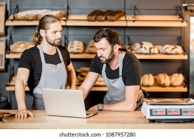 Two handsome sellers in uniform working with laptop standing at the counter of the bakery shop