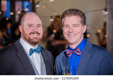 Two handsome smiling men in bow ties at a party