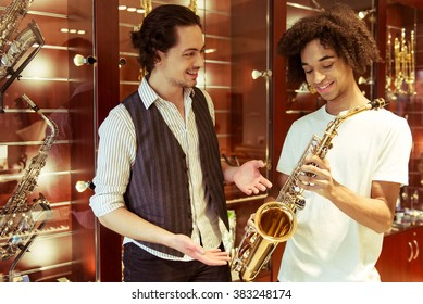 Two handsome stylish men holding a saxophone, talking and smiling while standing in a musical shop