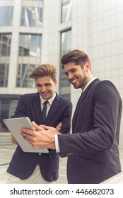 Two handsome young businessmen in classic suits are using a tablet and smiling, standing outside the office building