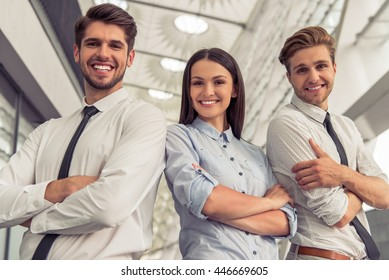 Two handsome young businessmen and lady in classic clothes are looking at camera and smiling, standing with crossed arms near the office building