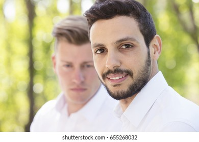 two handsome young man in white shirts standing outside and smiling at camera