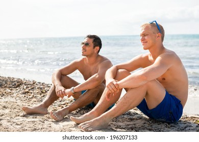 Two handsome young men chatting on a beach in their swimsuits sitting side by side on the sand with their backs to the ocean enjoying a relaxing summer day at the beach