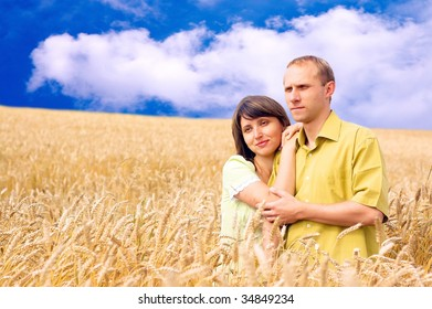 Two happiness people on the golden wheat field and blue sky