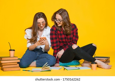 Two Happiness  smiling young woman gamer using smart mobile phone and playing games on isolated yellow color background, Lifestyle and leisure with hobby concept