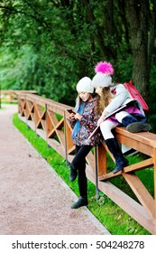 Two happy adorable preteen girls in colorful outfit close up portrait in the city park
