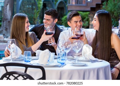 Two happy adult couples on double date in restaurant sitting at round table outdoors  holding glasses of red wine and looking at each other.