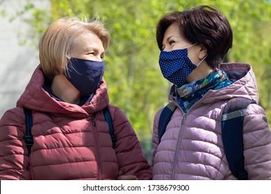 Zwei glückliche erwachsene Frauen, Freunde in Schutzmasken auf dem Gesicht lächeln, reden, gehen im Freien in der Stadt, Spaß zusammen haben. Coronavirus, Virus, soziale Distanz, covid-19 Konzept.