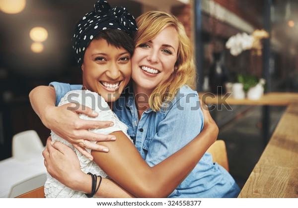 Dois feliz carinhoso jovem mulher abraçando um ao outro em um abraço próximo enquanto rindo e sorrindo, jovens amigas multiraciais