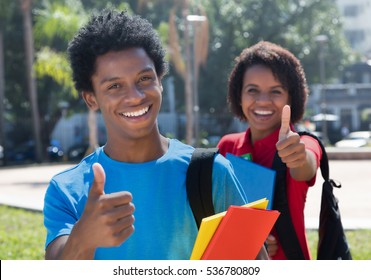 Two happy african american students on campus showing thumbs outdoor