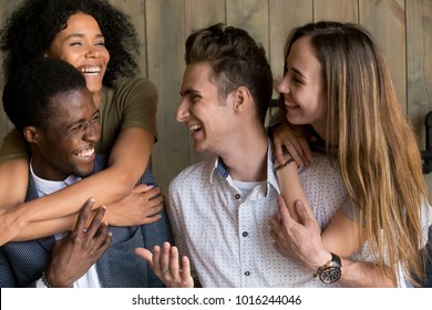Two happy african and caucasian couples embracing bonding having fun together, young cheerful diverse men and women in love hugging smiling laughing, multiracial friendship, racial diversity concept