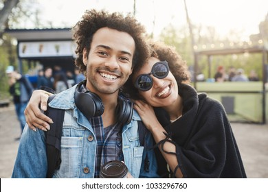 Two happy african-american travellers with afro hairstyle hugging and looking at camera, making photo while walking in park, expressing positive emotions. Friendship and relationship concept.