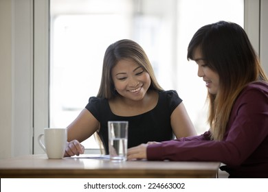 Two happy Asian business women having a meeting in an office.
