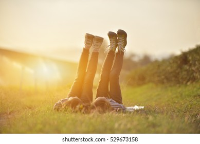 Two happy asian children lying on green grass outdoors and rise legs up in spring park,Fun concept.