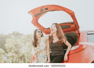 Two happy Asian girl best friends traveler laughing and smiling while sitting in red car trunk