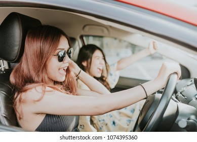 Two happy Asian girl best friends traveler laughing and smiling in car during a road trip to vacation.